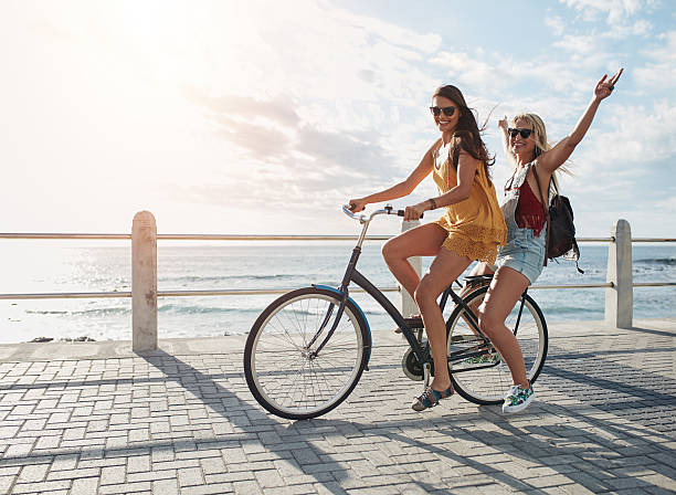 Best friends having fun on a bike Joyful young women riding a bicycle together. Best friends having fun on a bike at the seaside promenade. promenade stock pictures, royalty-free photos & images
