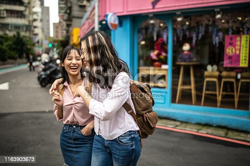 Two female Cheerful students walking  on spring day, wearing backpacks, talking and embracing