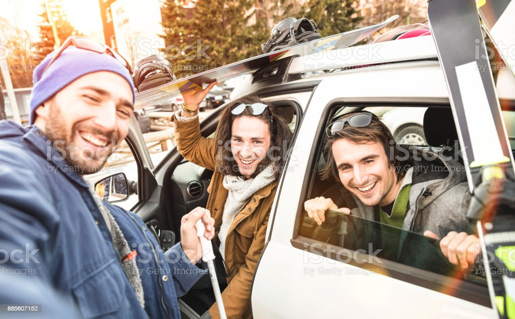 Best friends having fun taking selfie at car for ski and snowboard on mountain trip - Friendship hangout concept with young people loving winter sports travel - Vintage desaturated contrast filter stock photo