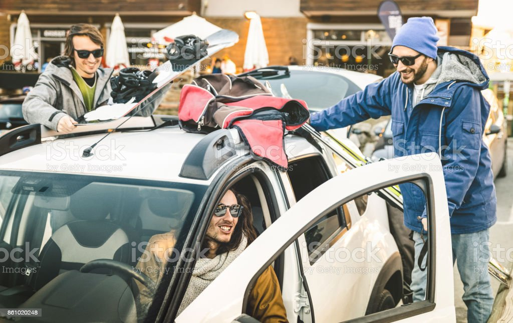 Best friends having fun together preparing car for ski and snowboard at mountain trip - Friendship hangout concept with young people loving winter sports travel - Vintage desaturated contrast filter stock photo