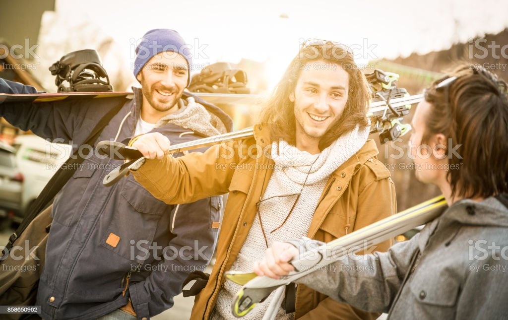 Best friends having fun together walking with ski and snowboard at mountain trip - Friendship concept with young people hangout loving winter sports travel - Warm filter with backlight sunshine halo stock photo