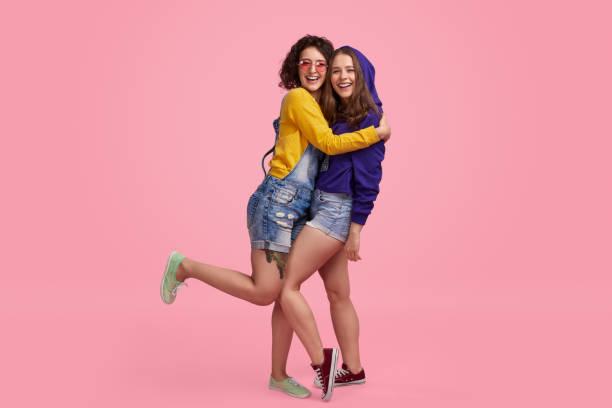melhores amigos que abraçam e que sorriem - lifestyle color background - fotografias e filmes do acervo