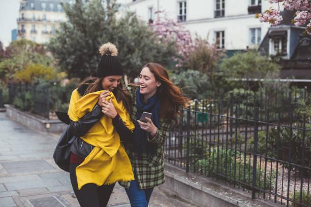 beste freunde in paris zu fuß, während sms - winterjacke lang damen stock-fotos und bilder