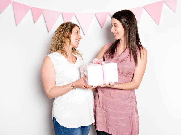 Les meilleures amies dans la douche de bébé fête célébrant donnant kid stuff comme cadeau - Photo