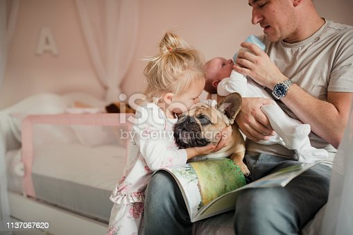 Father feeding his baby while his young daughter and puppy cuddle and kiss each other beside him.