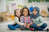 Two girls and a boy are indoors in their preschool classroom. They are smiling at the camera while sitting on the carpet and embracing.