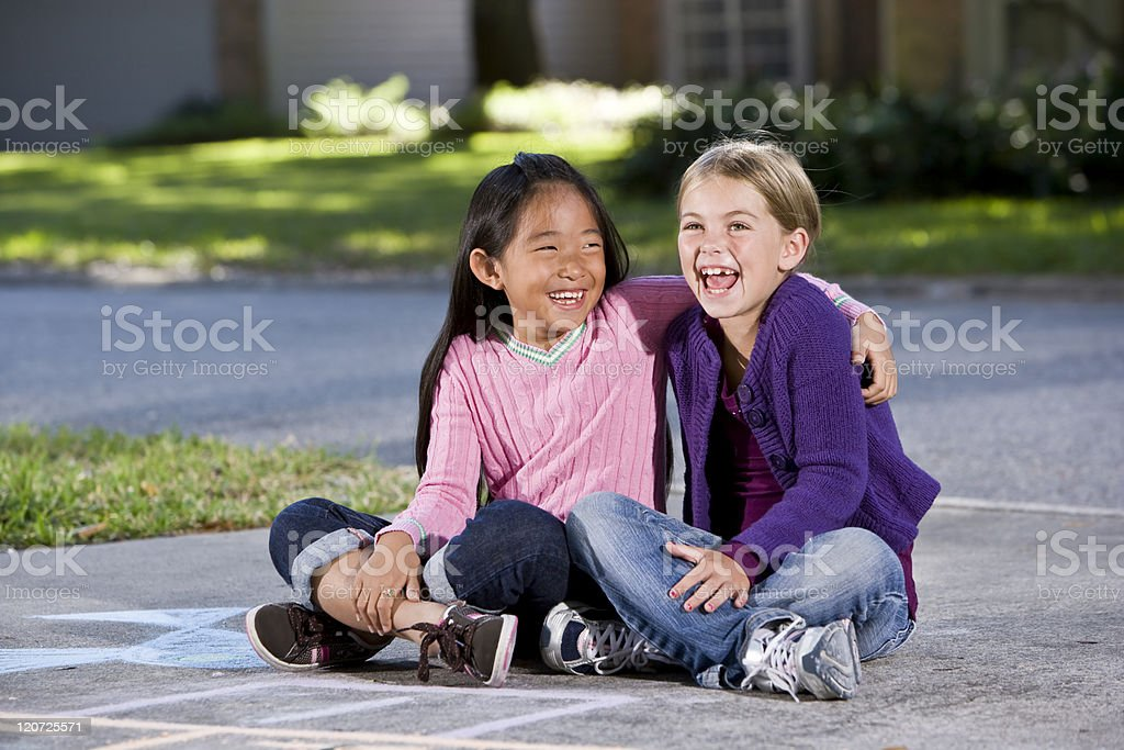 Best friends playing together on driveway royalty-free stock photo