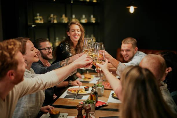Beste Freunde sitzen im Restaurant zum Abendessen und machen einen Toast mit Weißwein. Auf dem Tisch liegt Essen. – Foto