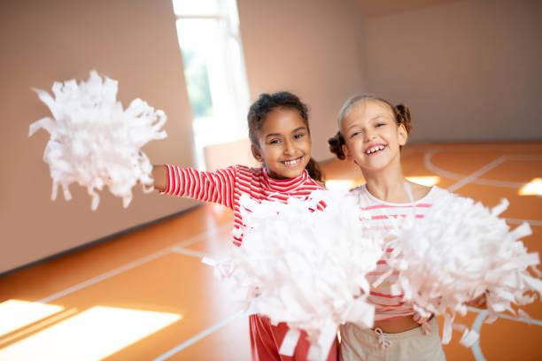 Beste Freunde lächeln beim gemeinsamen Üben von Cheerleading – Foto