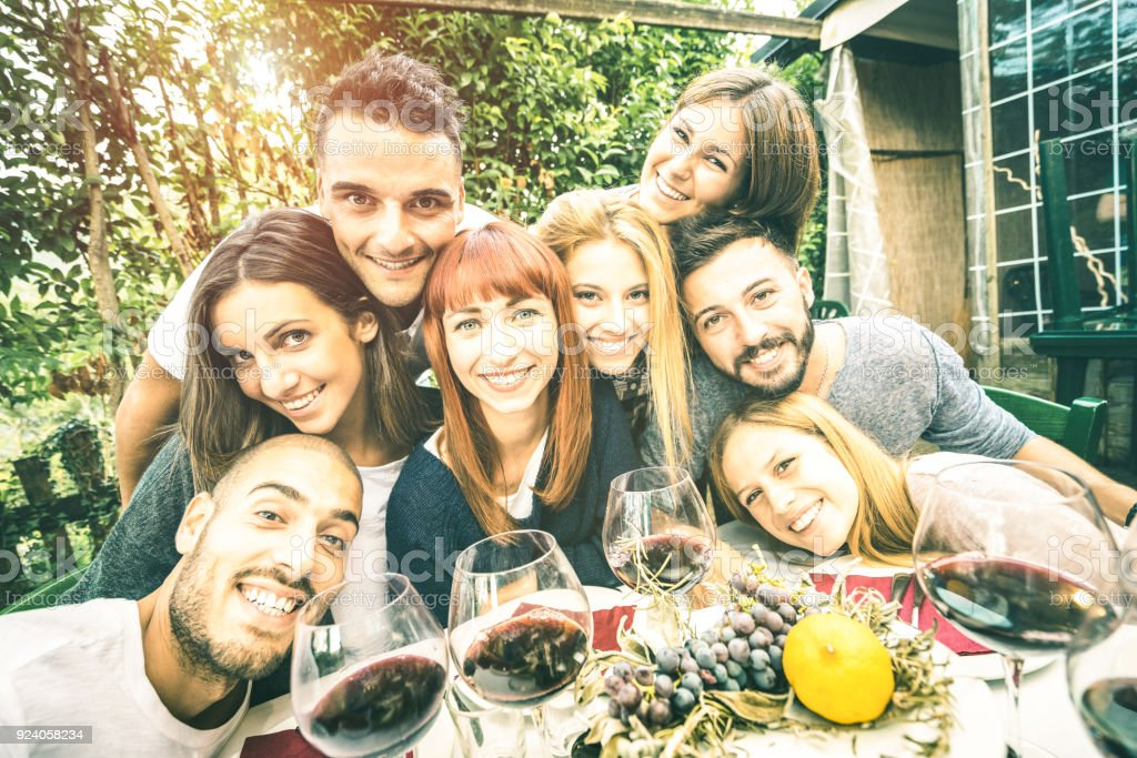 Best friends taking selfie at lunch party with serene faces - Happy youth concept with young people having fun together drinking wine - Cheer and friendship at grape harvest time - Bright retro filter stock photo