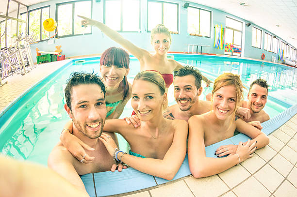 best friends taking selfie in swimming pool - happy friendship - competition group stock photos and pictures