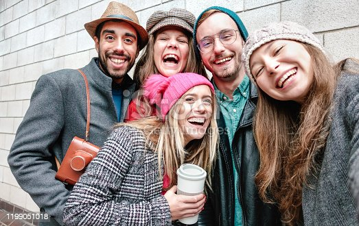 861023492 istock photo Best friends taking selfie on warm fashion clothes - Happy lifestyle concept with millenial people having fun together - Everyday life of next generation guys and girls enjoying friendship outdoors 1199051018
