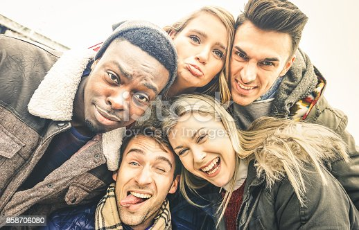istock Best friends taking selfie outdoor on autumn winter clothes - Happy youth concept with multiracial people having fun together - Cheer and friendship against racism - Vintage lomo desaturated filter 858706080