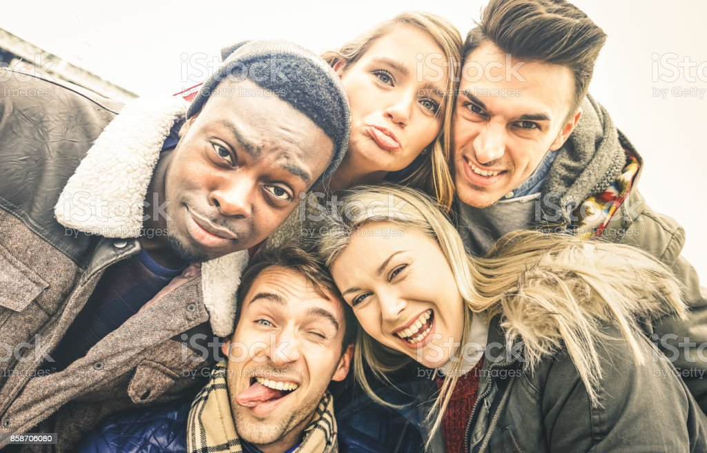Best friends taking selfie outdoor on autumn winter clothes - Happy youth concept with multiracial people having fun together - Cheer and friendship against racism - Vintage lomo desaturated filter - foto stock