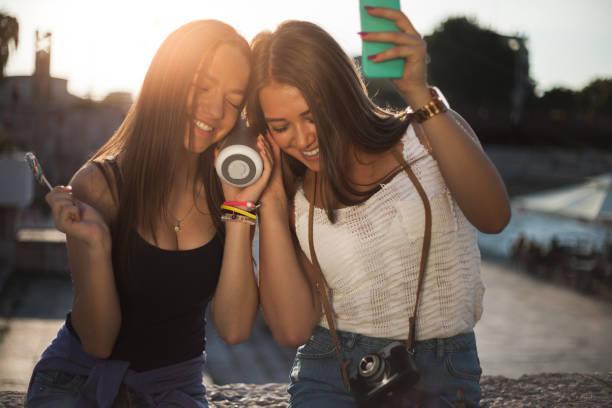 Mejores amigos juntos al aire libre mientras escucha música - foto de stock