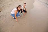 istock Best friends Two Young woman drawing smiley shape in sand Relaxation at the sandy beach by the sea. Healthy Lifestyle, Beach holiday 1227093778