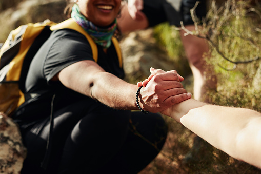 Cropped shot of two young women reaching for each other's hands on a hiking trail
