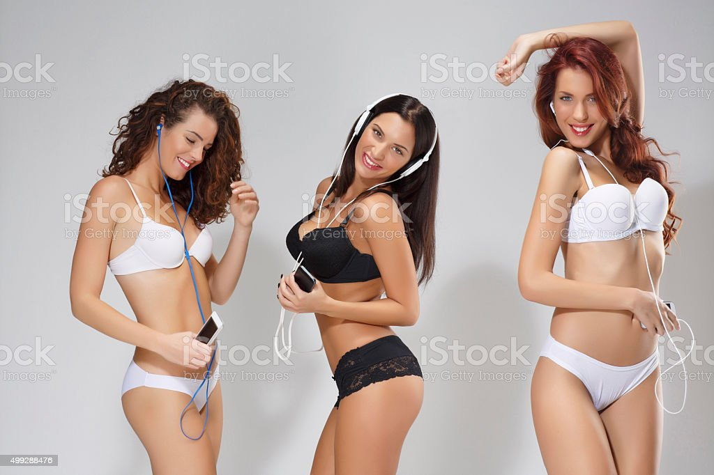 Best friends   Young women listening  music  to headphones and dancing stock photo