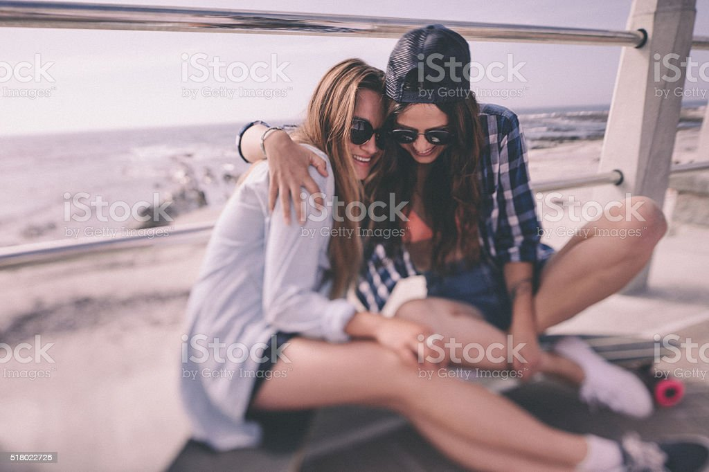 Best girl friends in hipster clothing at the beach front stok fotoğrafı