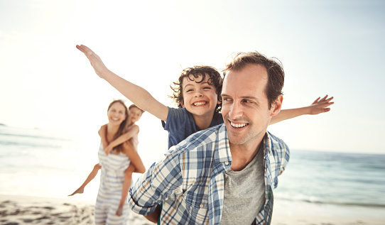 Shot of a happy young family having fun at the beach