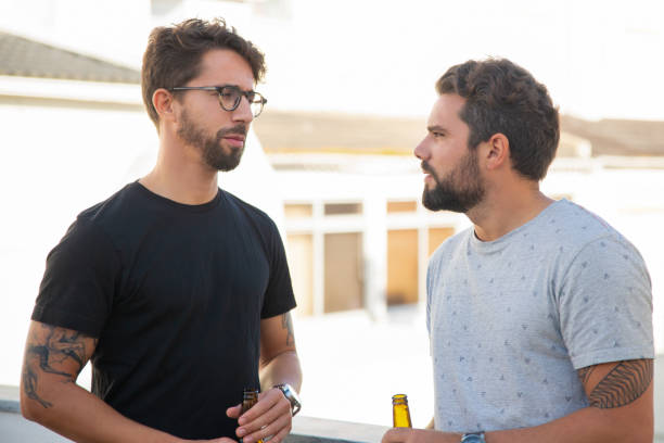 Best male friends discussing issues over bottle of beer stock photo