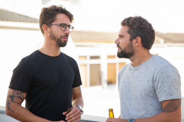 Beste männliche Freunde diskutieren Fragen über Flasche Bier – Foto