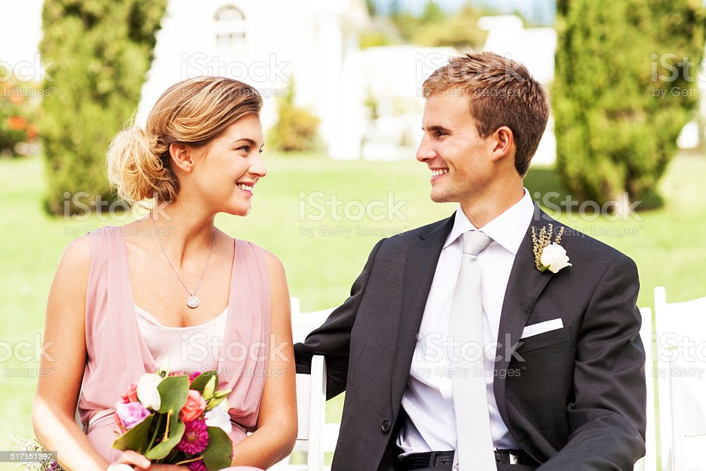Best Man And Bridesmaid Looking At Each Other During Wedding stock photo