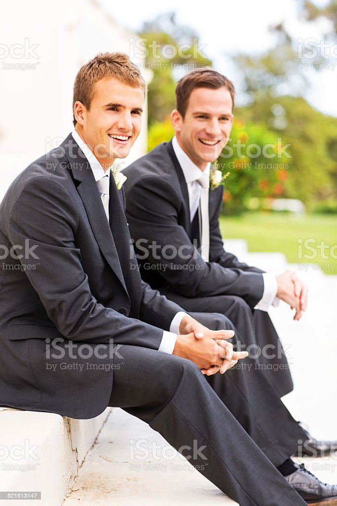 Best Man And Groom Sitting Together In Garden stock photo