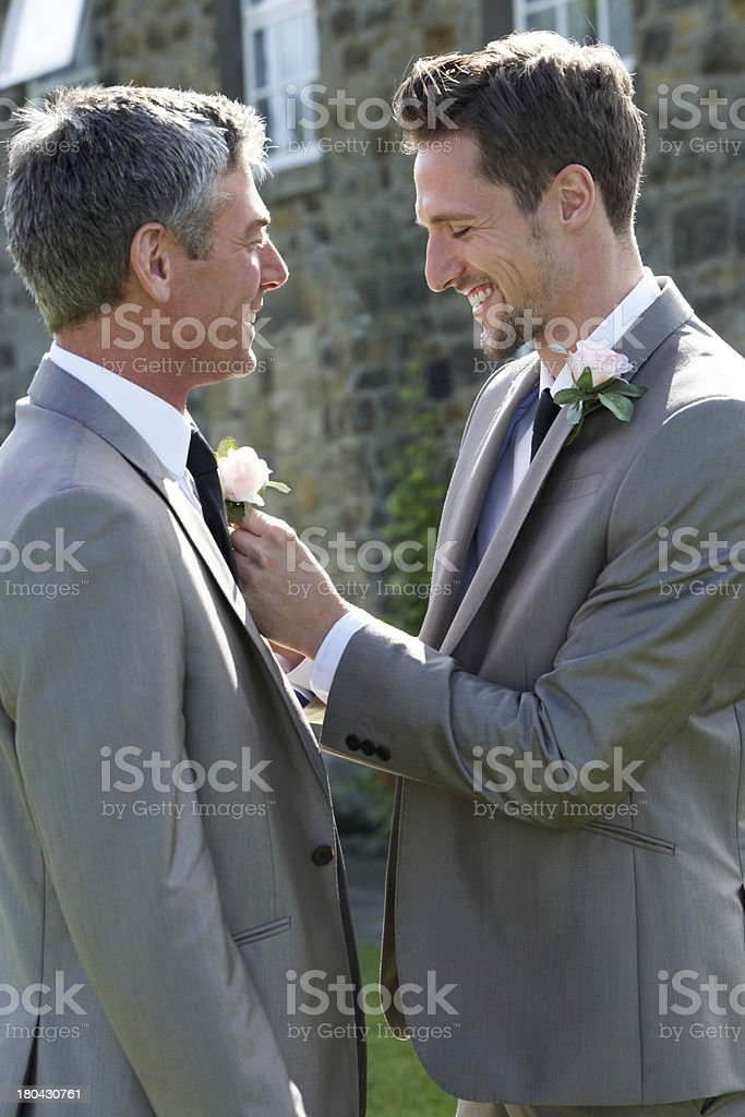 Best man and groom smiling at a wedding stock photo