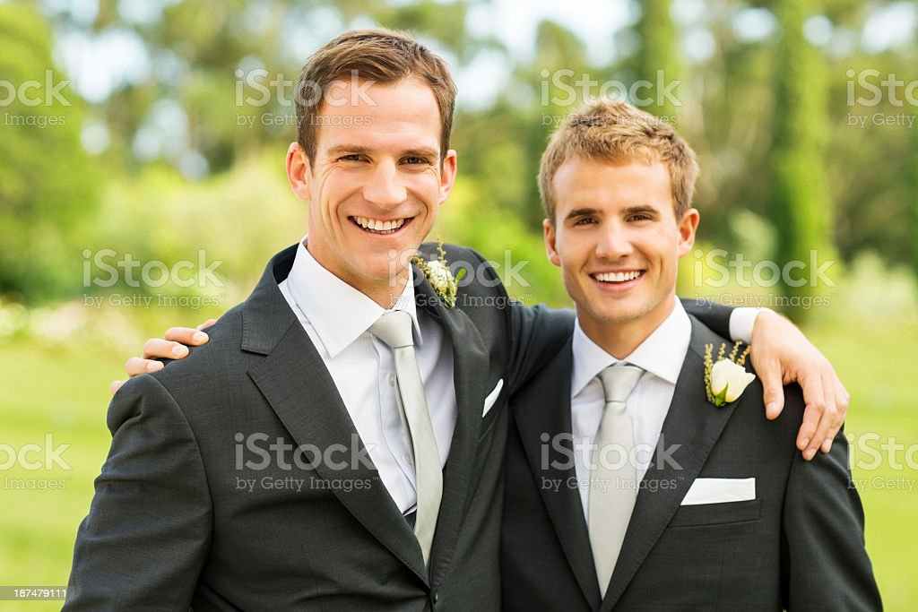 Best Man And Groom Standing Together In Garden stock photo