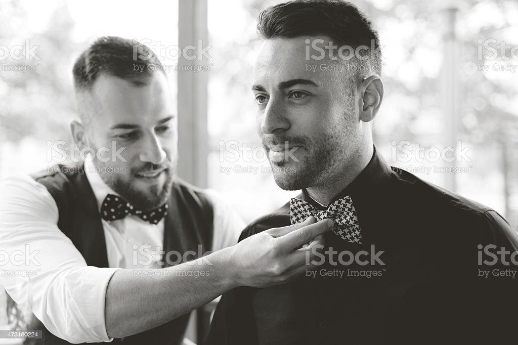 Best man fixing groom's bow tie stock photo