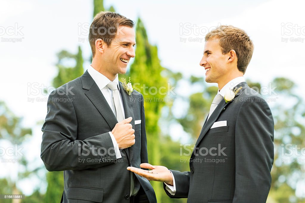 Best Man Looking At Groom While Showing Wedding Rings stock photo