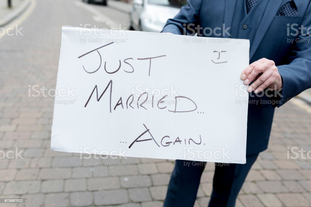 Best man or groom holding a homourous hand written sign stating Just married...again at a second wedding or renewal of vows in the UK stock photo