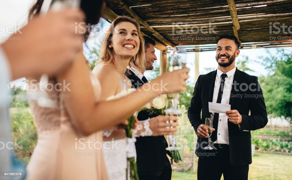 Best man performing speech for toast at wedding reception stock photo