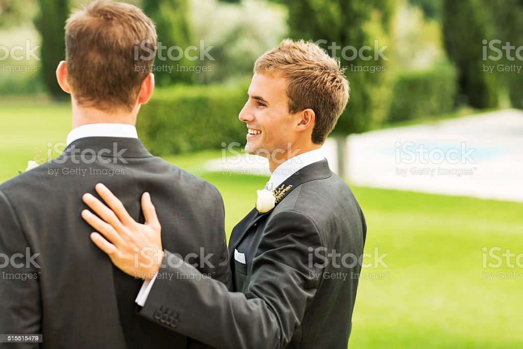Best Man Smiling While Keeping Hand On Groom's Back stock photo