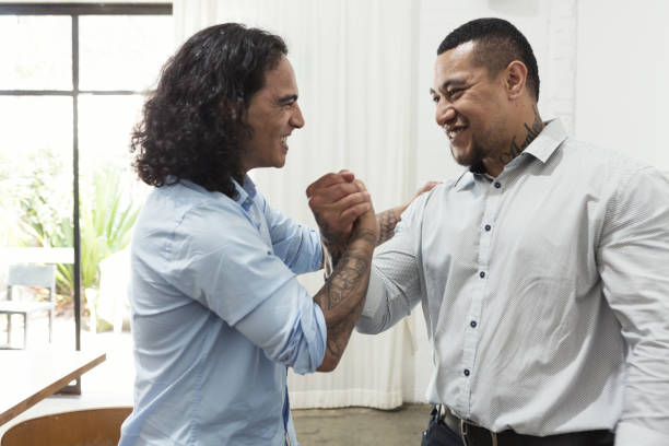 Best mates greeting each other with an emotional handshake stock photo