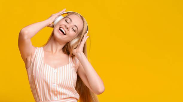 Best Music App. Teen Girl Listening Favorite Song In Wireless Headphones Best Music App. Carefree Teen Girl Listening Her Favorite Song In Wireless Headphones wireless headphones stock pictures, royalty-free photos & images