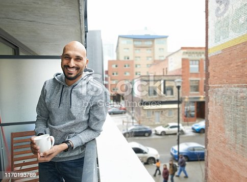 Shot of smiling young man standing in the balcony with cup of coffee