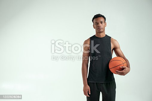 Best player. Handsome young african man in sport clothing carrying a basketball ball and looking at camera while standing against grey background. Basketball. Sport concept