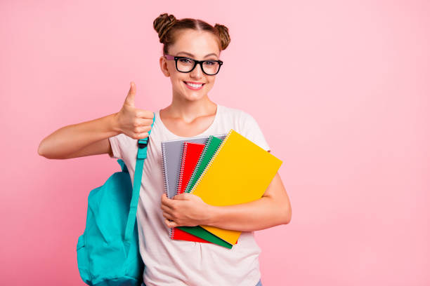 Best school year! Portrait of sweet and cute girl hold colored notebook in hand and show thumb up isolated on shine pink background with copy space for text Best school year! Portrait of sweet and cute girl hold colored notebook in hand and show thumb up isolated on shine pink background with copy space for text nerd hairstyles for girls stock pictures, royalty-free photos & images