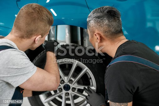 Two male mechanics using torch for inspecting wheel of lifted car at auto repair shop. Car service, repair concept. Rear view. Focus on men. Horizontal shot