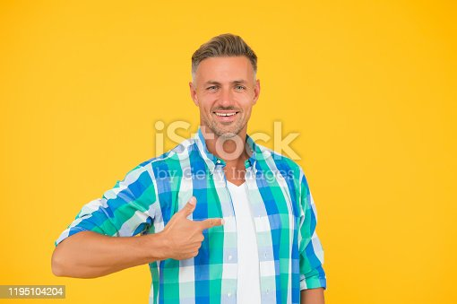 istock best shopping here. mature man bearded face. smiling guy pointing finger, copy space. male fashion model shirt. presenting product. goods for men. summer sales here. sexy man yellow background 1195104204
