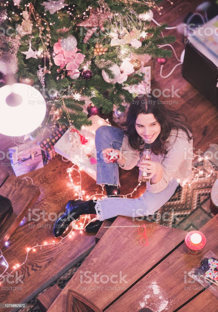 Best thing are packed in Small boxes! Women in front of the christmas tree. stock photo