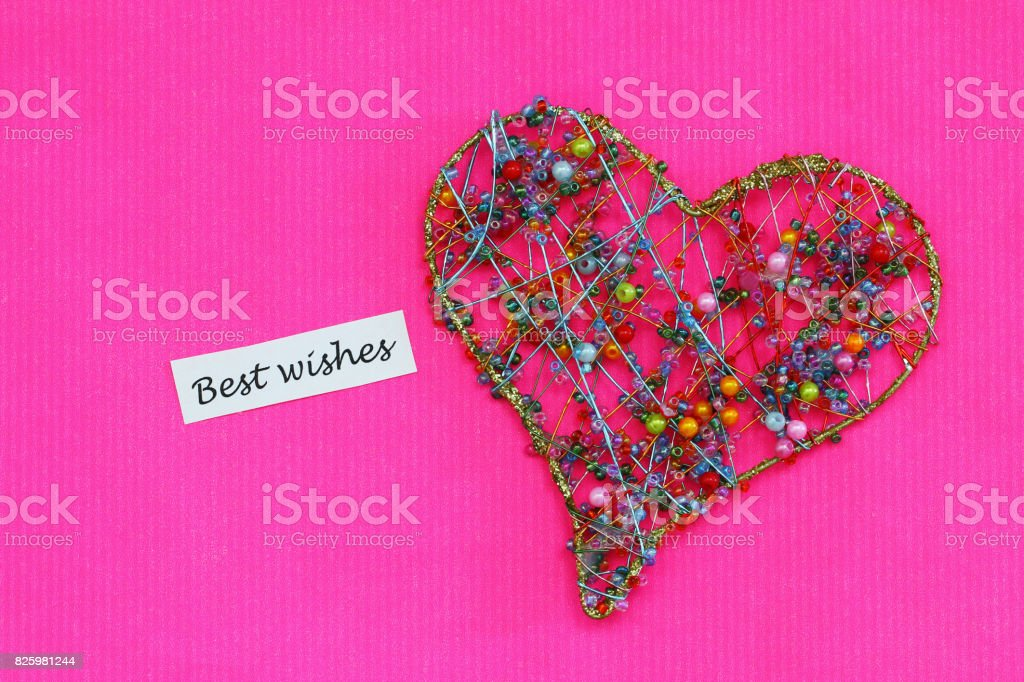 Best wishes card with heart made of colorful beads on pink background stock photo