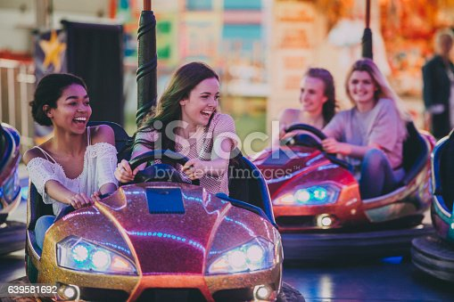 A group of girls, two teams in dodgems trying to bump others, laughing and having fun!