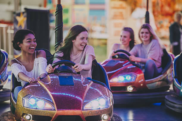 bestfriends driving dodgems - carnival stock photos and pictures