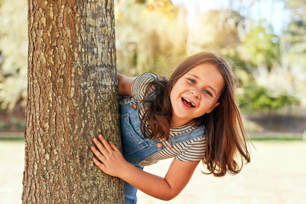 Bet you didn't see me hiding here! Portrait of a little girl playing at the park hide and seek stock pictures, royalty-free photos & images