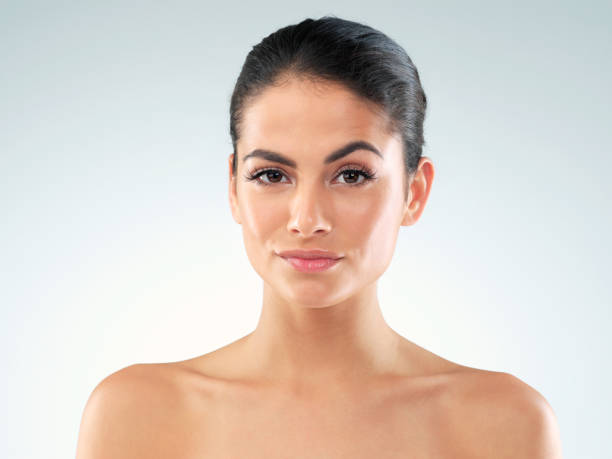 Bet you want to know my beauty secrets Studio shot of an attractive young woman posing against a gray background raised eyebrows stock pictures, royalty-free photos & images