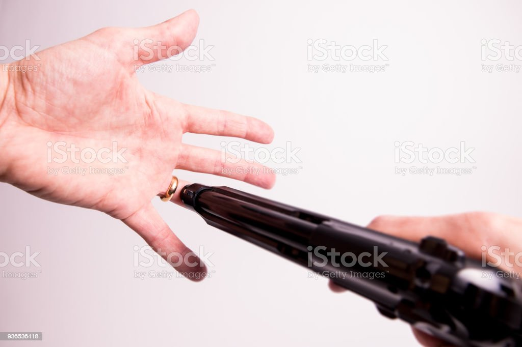 Betrayed guy is shooting his wedding ring off from his finger stock photo