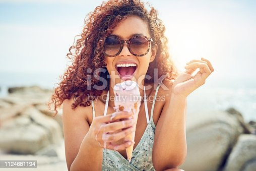 Cropped portrait of an attractive young woman eating a melting ice cream while sitting on the beach